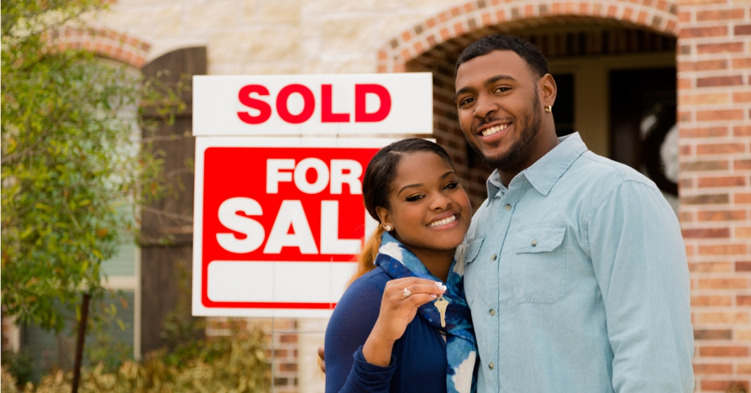 couple-in-blue-with-just-sold-sign-and-house-key